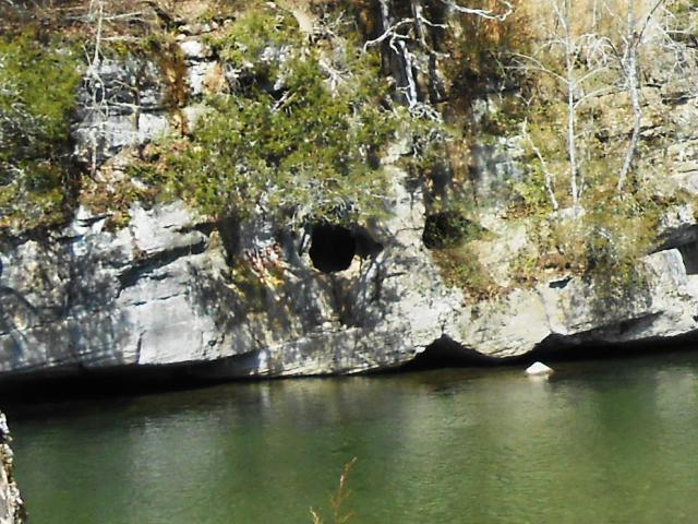 "The hole in the rocks across the river is labeled ""Webb Cave"". Looks quite tight!"